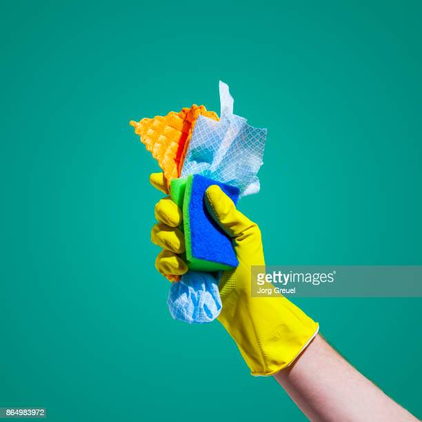 Hand in rubber glove holding cleaning cloths and a sponge