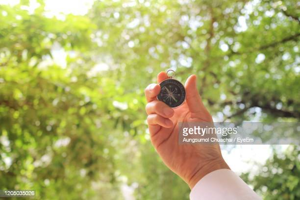 a hand in white shirt holding a compass, just meaning the new way to successful.  keep walking. - aungsumol stock pictures, royalty-free photos & images