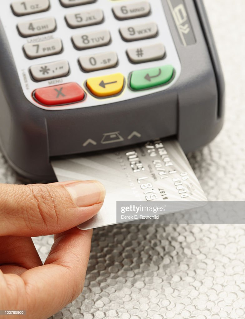 Hand inserting credit card into machine : Stockfoto