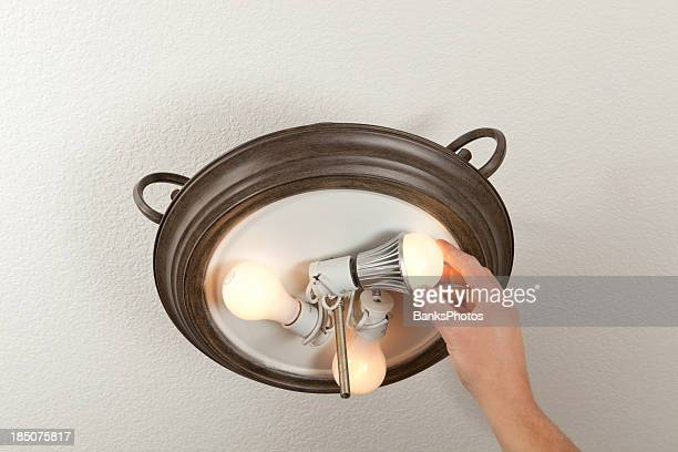 Hand Installing LED Light Bulb into a Ceiling Fixture