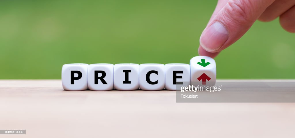 Hand is turning a dice and changes the direction of an arrow symbolizing that the price is going down (or vice versa) : Stock Photo