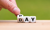 Hand is turning a dice and changes the word Pay to Day