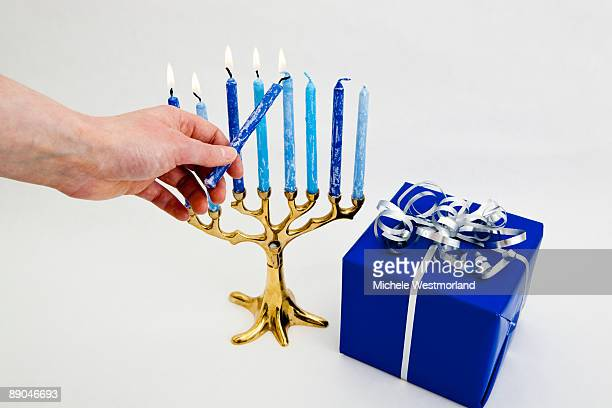 Hand Lighting Candles in Hanukkah Menorah