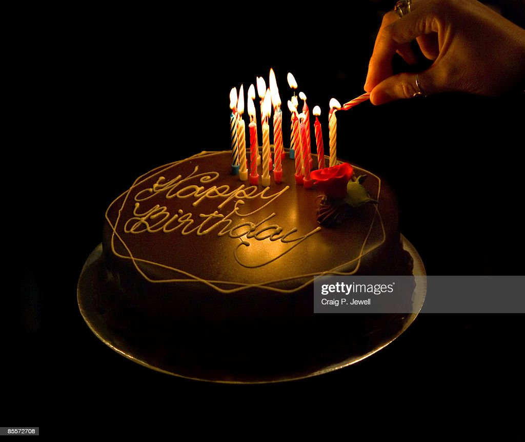 Hand Lighting Candles On A Chocolate Birthday Cake Stock Photo