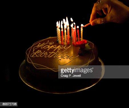 Hand Lighting Candles On A Chocolate Birthday Cake Stock