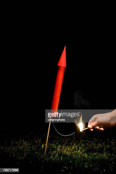 hand lighting red rocket/fireworks fuse - fuse stock photos and pictures