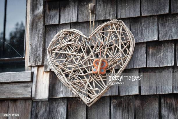 a hand made heart of straw on a wall with shingles - herpes zoster fotografías e imágenes de stock
