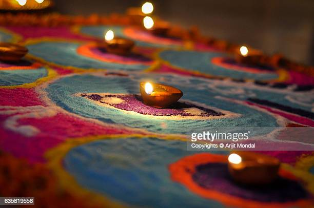 Hand made oil lamps decorated with Rangoli in the festive night of Hindu festival Diwali or Deepavali