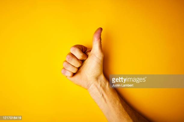 hand making the thumbs up signal on yellow backdrop - agreement stock pictures, royalty-free photos & images