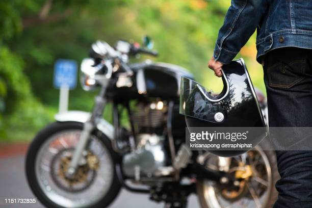 hand man holding a helmet and  motorcycle blur background. - charging sports stock pictures, royalty-free photos & images