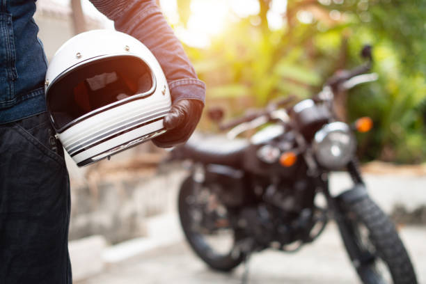 hand man holding a helmet and motorcycle blur background. - asian guy riding a motorcycle with helmet stock pictures, royalty-free photos & images