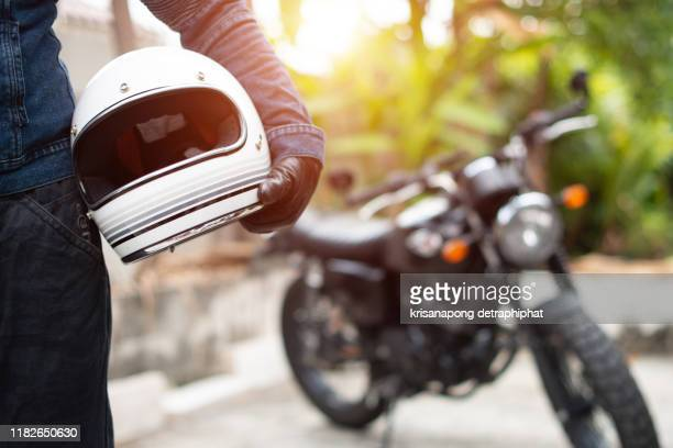 hand man holding a helmet and motorcycle blur background. - バイクヘルメット ストックフォトと画像