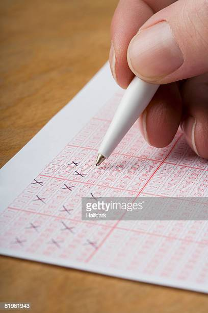 a hand marking a lottery ticket - lotterytickets stock pictures, royalty-free photos & images