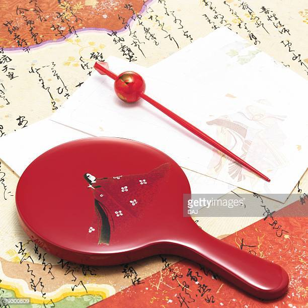 Hand mirror and Japanese hairpin on paper written Japanese poem, high angle view