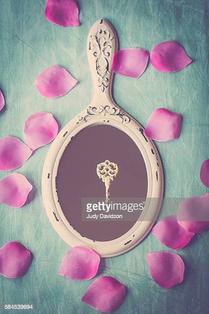 Hand mirror with ornate key and pink rose petals on aqua background