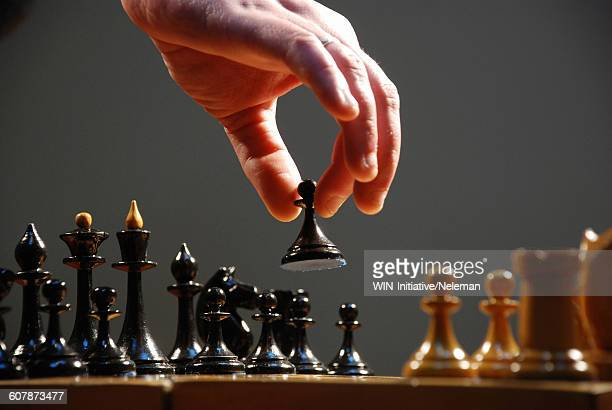 hand moving the pieces of a chess board, close-up - chess stock pictures, royalty-free photos & images