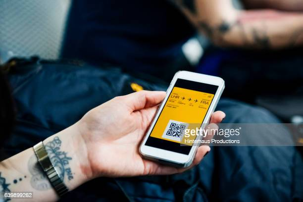 Hand of a backpacker showing smart phone with boarding pass