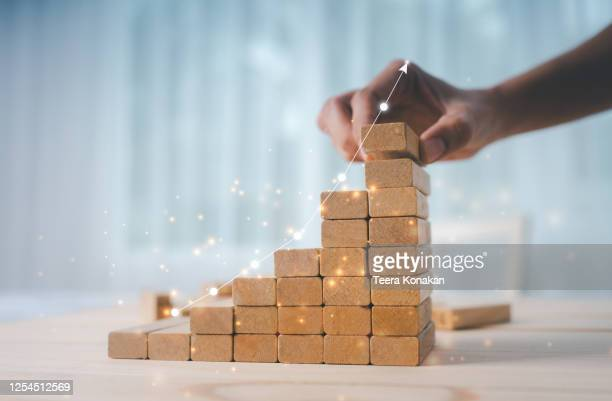 hand of a businesswoman is arranging wooden toys as steps along the rising graph. - arranging stock pictures, royalty-free photos & images