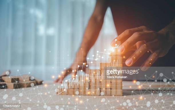hand of a businesswoman is arranging wooden toys as steps along the rising graph.concept for business growth success process - effectiviteit stockfoto's en -beelden