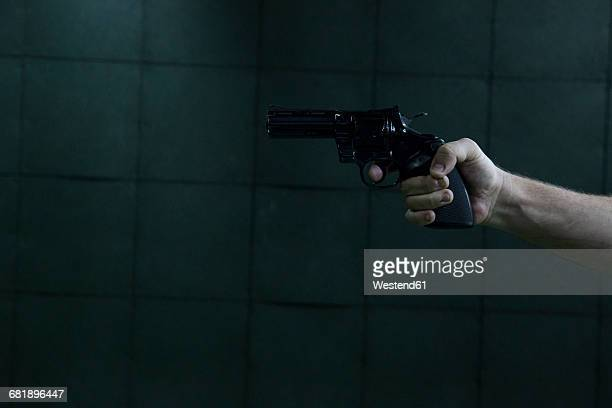 hand of a man aiming with a revolver in an indoor shooting range - sportschießen stock-fotos und bilder