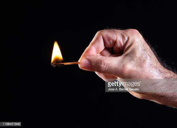 hand of a man, flame and smoke of match on black background. - fiammifero foto e immagini stock