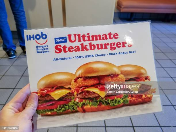 Hand of a man holding a menu with images of several burgers as well as IHoB logo following pancake restaurant International House of Pancake's...