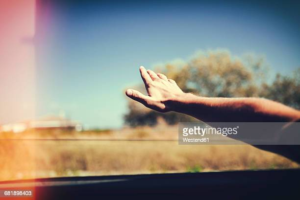 Hand of a man leaning out of car window