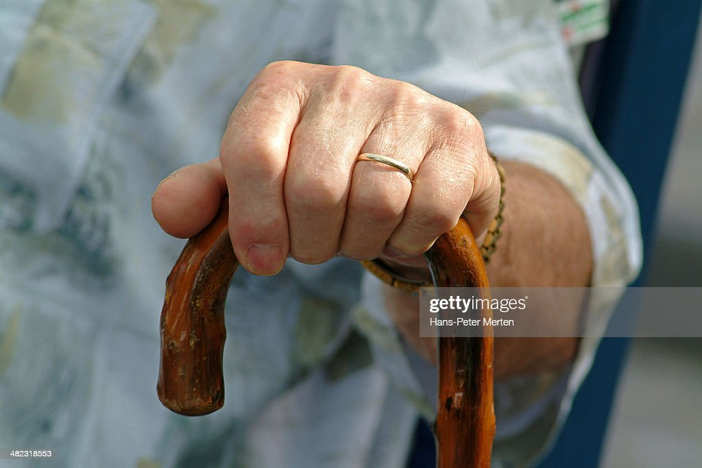hand of a man on walking stick : Stock Photo