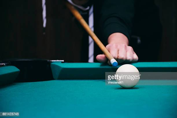 Hand of a man playing pool billard in a bar