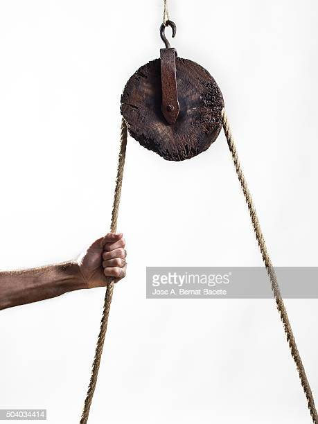 Hand of a man pulling strongly a rope that happens for a pulley of ancient wood