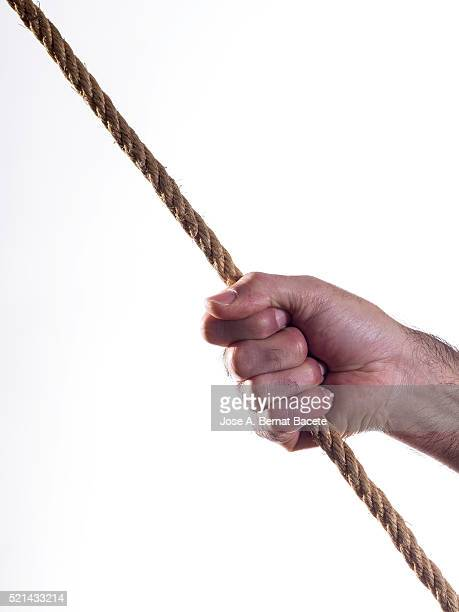 Hand of a man seized to a rope and throwing strongly
