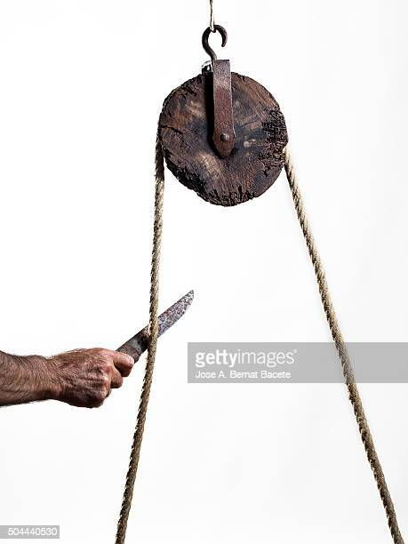 Hand of a man with a knife cutting a rope that happens for a pulley