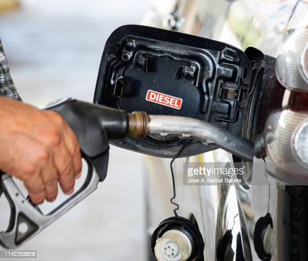 hand of a men from with a hose of fuel refueling a diesel vehicle with self serve pump and hose. spain. - diesel stock pictures, royalty-free photos & images