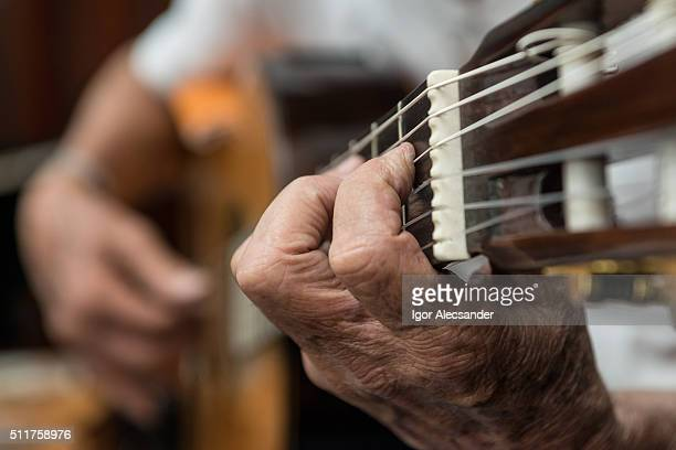 Hand of a old man playing a Chorinho music in a acoustic guitar, Brazil
