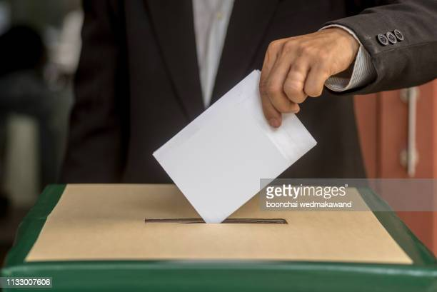 hand of a person casting a vote into the ballot box during elections - démocratie photos et images de collection