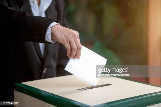 hand of a person casting a vote into the ballot box during elections - election stock pictures, royalty-free photos & images