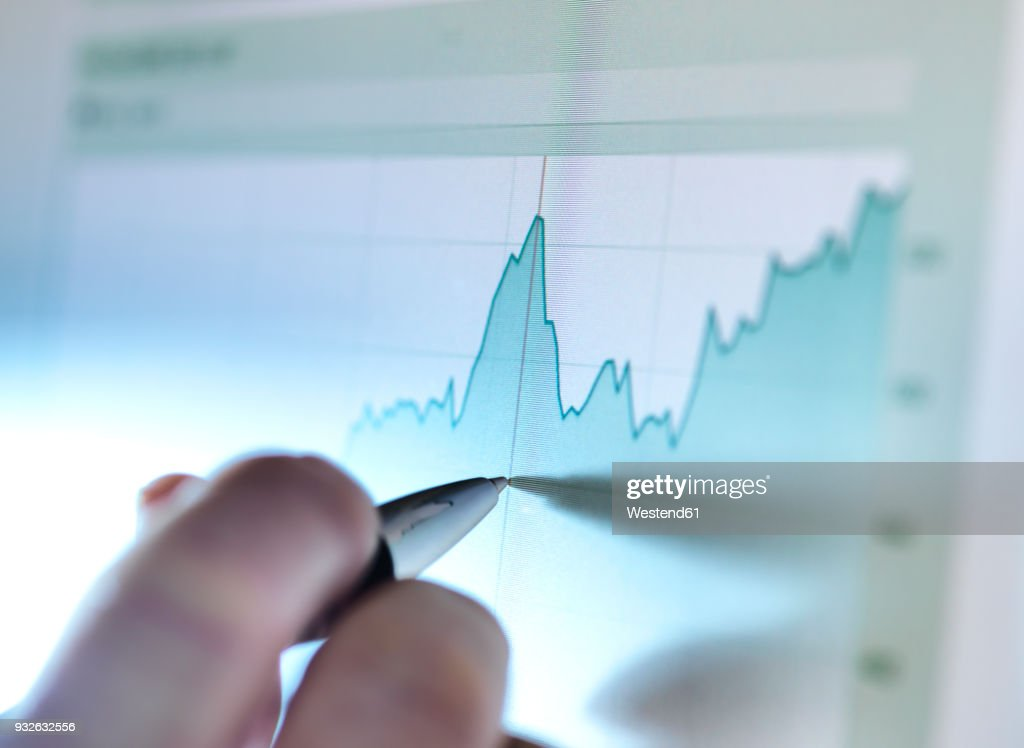 Hand of a stock broker analysing line graph on computer screen : Stock Photo