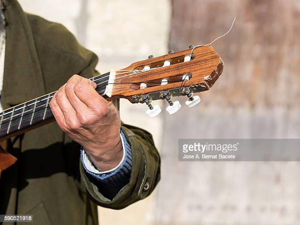 Hand of a street musician tuning a Spanish guitar
