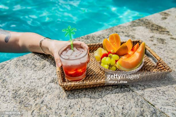 hand of a woman eating fruits and drinking caipirinha next to the pool in a sunny day in the summer time - brazil stock pictures, royalty-free photos & images