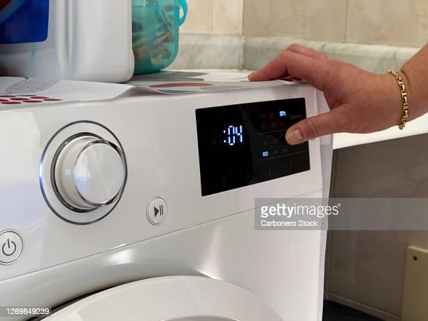 a hand of a woman pressing display of the washing machine - 電化製品 ストックフォトと画像