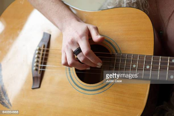 hand of a woman strumming the guitar - acoustic guitar stock pictures, royalty-free photos & images
