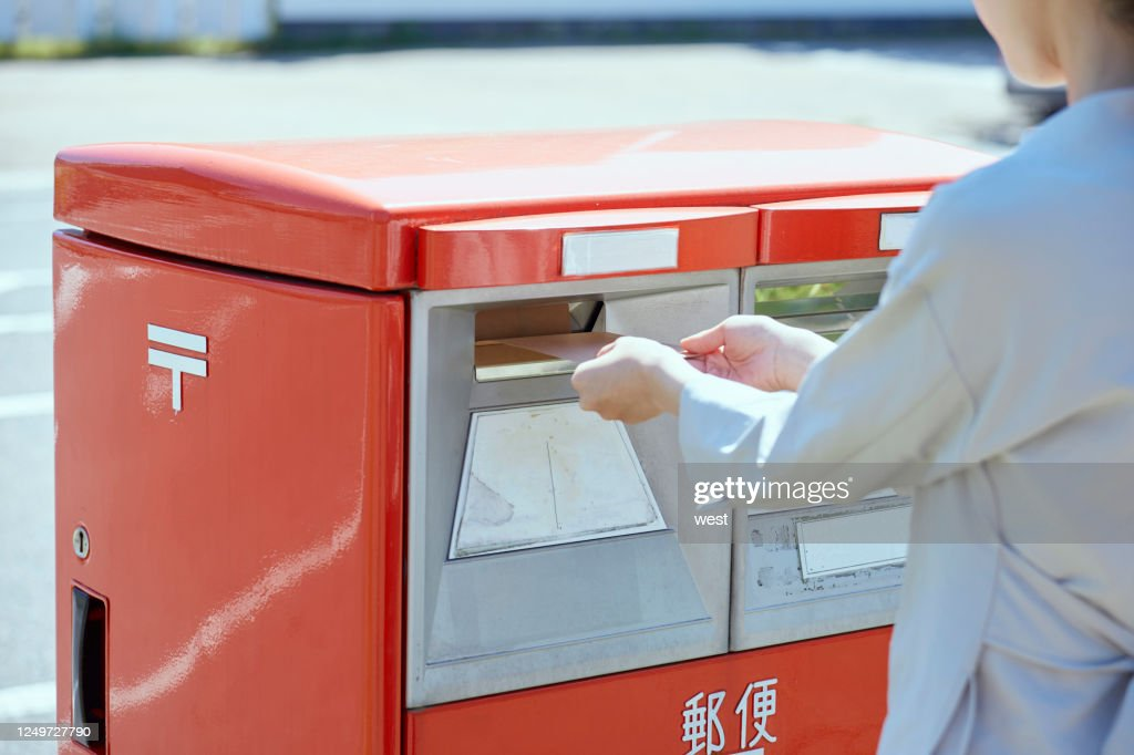 Hand of a young woman putting an envelope in a post box : Stock Photo