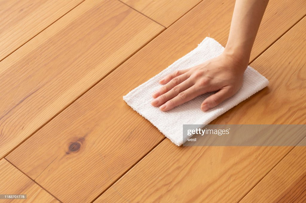 Hand of a young woman wiping the wood floor with a rag : Stock Photo