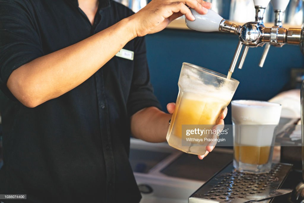 Hand of bartender pouring a lager beer in tap. : Stock Photo