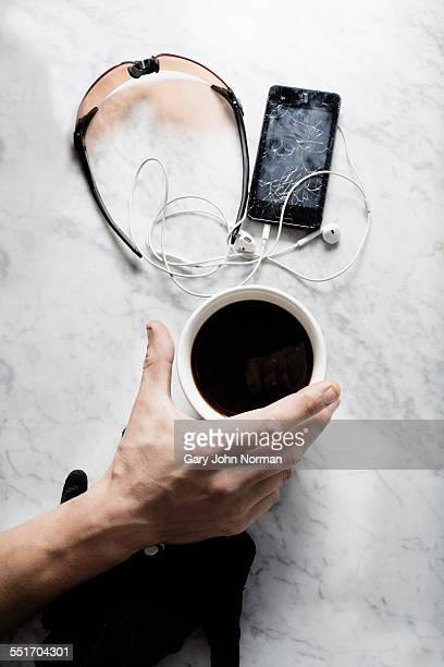 Hand of bike messenger with coffee, glasses, broken smartphone
