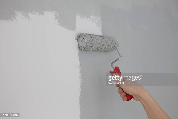 Hand of boy painting wall with paint roller