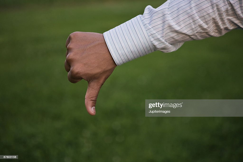 Hand of businessman gesturing thumbs down : Stock Photo