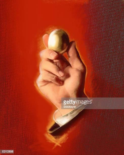Hand of businessman holding golden egg