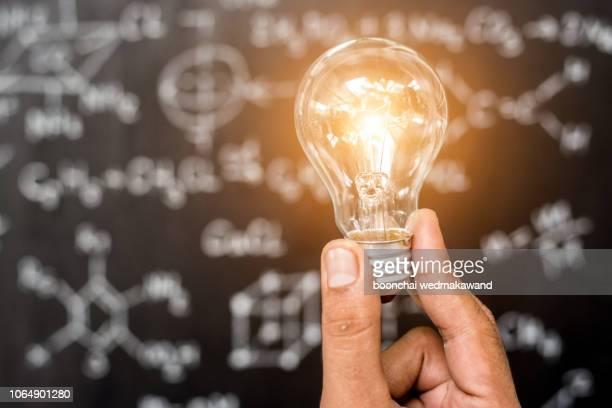 hand of businessman holding illuminated light bulb, idea, innovation and inspiration concept. - contraptie stockfoto's en -beelden