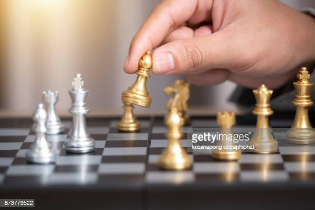 hand of businessman playing chess.